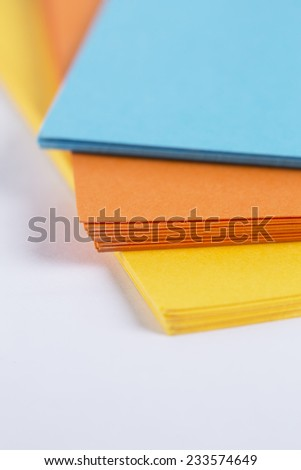 yellow, orange and blue cardboard on a white table - stock photo