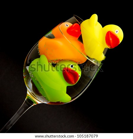 Yellow, orange and green rubber duck in a wineglass with water (black background) - stock photo