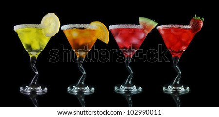 yellow, orange, pink and red martini drinks on black background