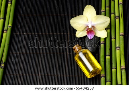 Yellow orchid and parfume bottle and on mat - stock photo
