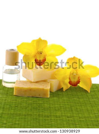 Yellow orchid with natural handmade soap, massage oil on green mat - stock photo