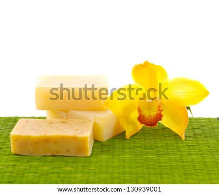 Yellow orchid with natural handmade soap on green mat - stock photo