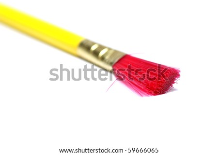 Yellow paint brush with red bristles on white background