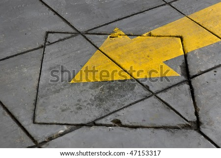Yellow painted arrow sign on pavement. - stock photo