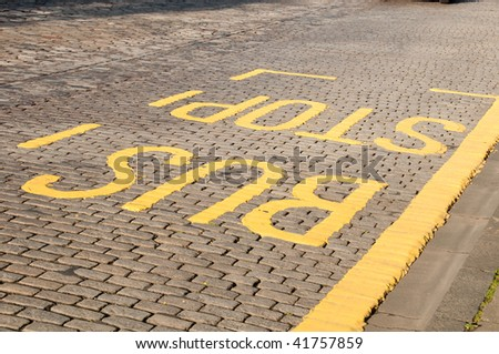 yellow painted BUS STOP sign on a paved street - stock photo