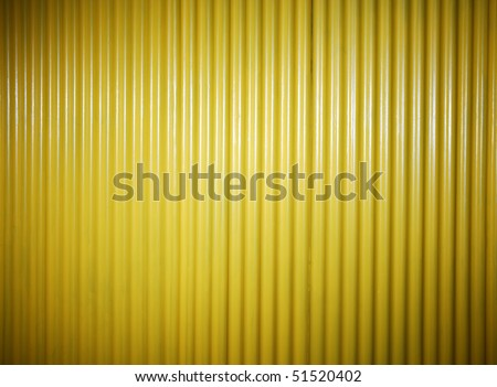 yellow painted corrugated fence background. spot light - stock photo