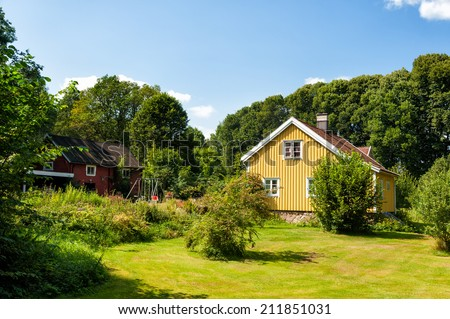 Yellow painted wooden cottage in Sweden - stock photo