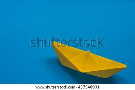 Yellow paper boat on blue background