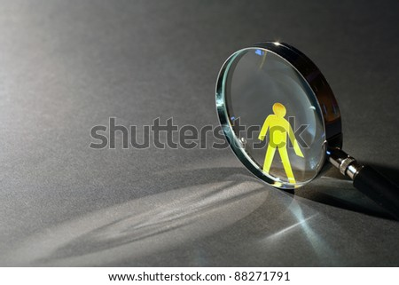 Yellow paper man near magnifying glass on dark background with beam of light - stock photo