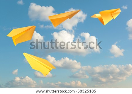 Yellow paper planes flying - stock photo