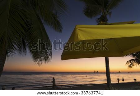 yellow parasol at a beautiful tropical beach during sunset - stock photo