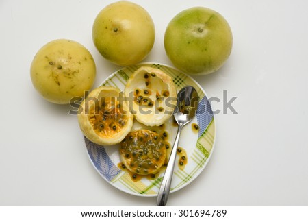 Yellow Passion fruits raw and cut open in half  isolated on white background. India. Sweet fruit juice-pulp with small black seeds. - stock photo