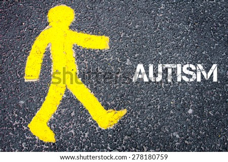Yellow pedestrian figure on the road walking towards AUTISM. Conceptual image with Text message over asphalt background. - stock photo