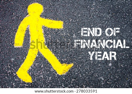 Yellow pedestrian figure on the road walking towards END OF FINANCIAL YEAR. Conceptual image with Text message over asphalt background. - stock photo