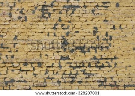 Yellow peeled brick wall background - stock photo