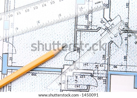 Yellow pencil and setquare and protractor on top of a blue floor plan.