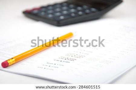 Yellow pencil on the printed stock graphs and charts, analyzing, calculator unfocused - stock photo