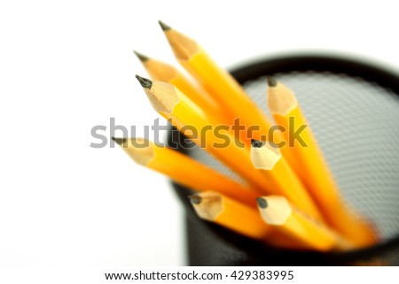 Yellow pencils in a pencil holder on white background