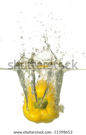 Yellow Pepper splashing on water in white background.A background of bubbles forming in blue water after yellow pepper are dropped into it.