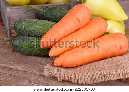 Yellow peppers in crate with cucumbers and carrots on table close up