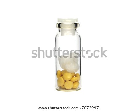 Yellow pharmaceutical pills in glass bottle on a white background