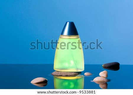 Yellow phial and  several stones in the water. - stock photo