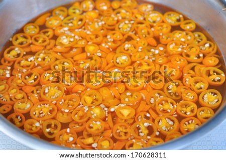 Yellow pickled-chilli mix with vinegar - stock photo