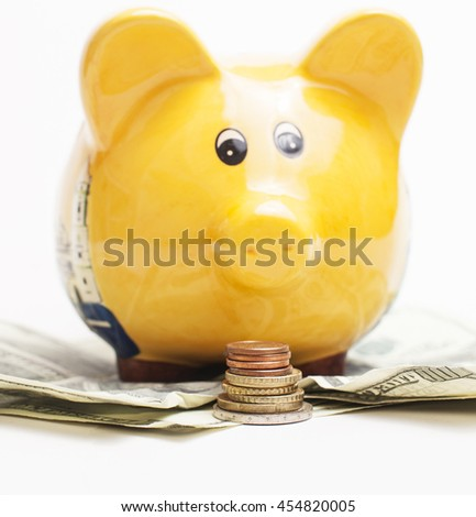 Yellow piggy bank and Stack of money coins isolated over the white background lot dollar cash under it - stock photo