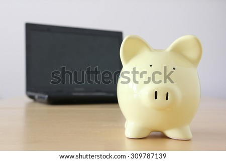 Yellow piggy bank on bright background, savings on computer.