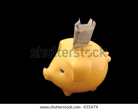 yellow piggy bank with money in it on black background - stock photo