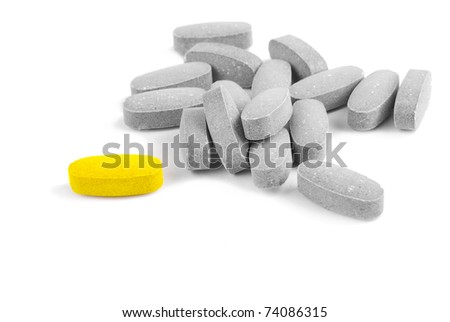 Yellow pill in a group of grey ones isolated over white - stock photo