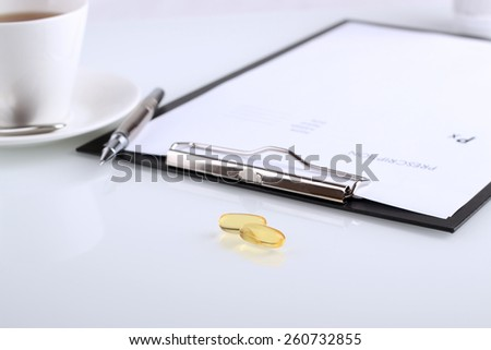 yellow  pills and   prescription on a table  - stock photo