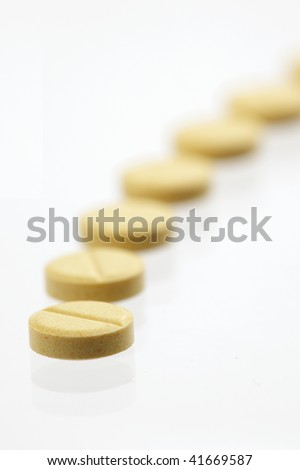 Yellow pills in a row on white background