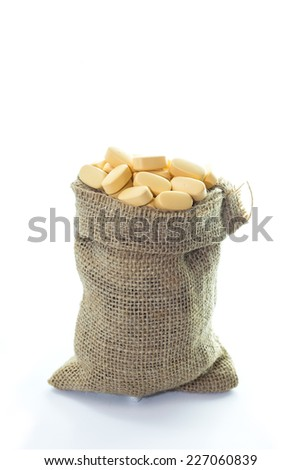 Yellow pills in Empty burlap sack isolated on white background