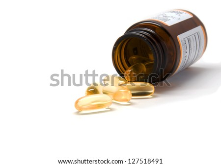 Yellow pills with dha and a bottle - stock photo