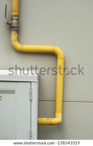 yellow pipes and gas meter on gray wall - stock photo