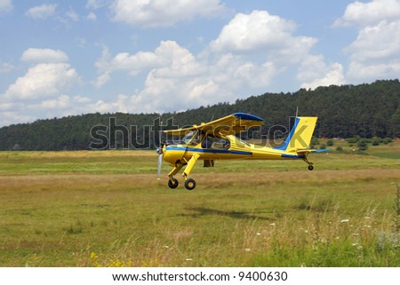 Yellow plane taking off