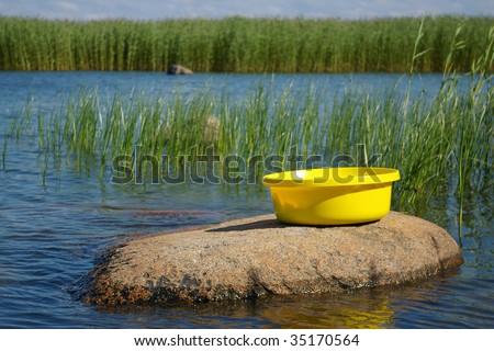 yellow plastic basin on stone by sea - stock photo