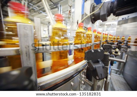 Yellow plastic bottles with light beer go on conveyor belt at large brewery. - stock photo