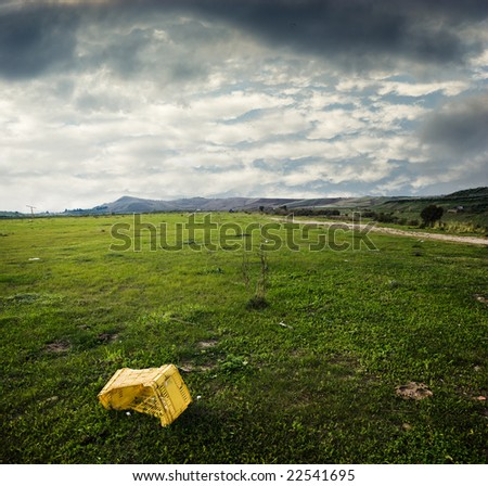 yellow plastic box abandoned in desolate grass area - stock photo