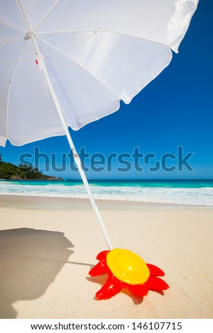 yellow plastic frisbee in the sand under a white sunshade at the beach c