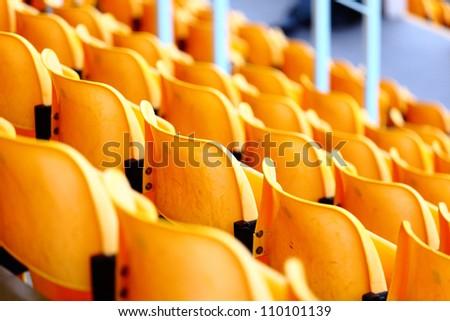 yellow plastic seats at stadium - stock photo