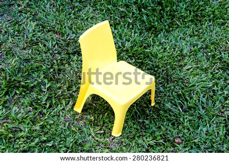 yellow plastic small chair put on turf - stock photo