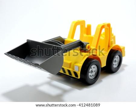 Yellow Plastic Toy Bulldozer  on White Background - stock photo