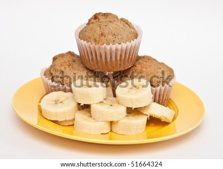 Yellow plate of sliced fresh banana and home-baked muffins. - stock photo