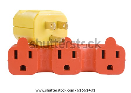 Yellow plug on an orange outlet surge adapter on a white background. - stock photo