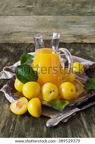 Yellow plum juice in a glass jug and ripe yellow plum on a vintage wooden table. Bio healthy food and drink. Organic diet. Toned image - stock photo