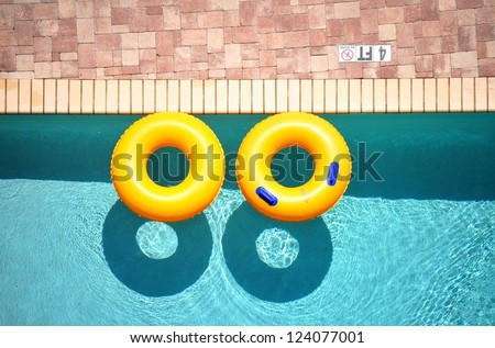Yellow pool float, pool ring in cool blue refreshing blue pool - stock photo