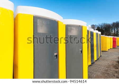yellow portable toilets under a nice cloudy sky - stock photo