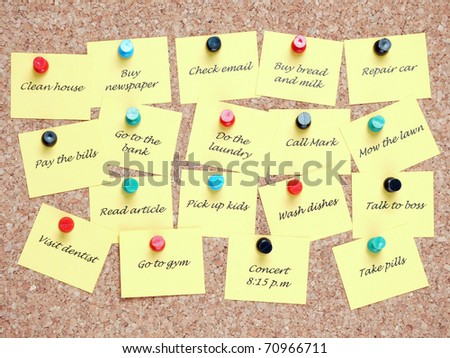 Yellow post it notes with various written to-do tasks affixed to the corkboard - stock photo